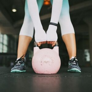 Girl lifting a kettle bell